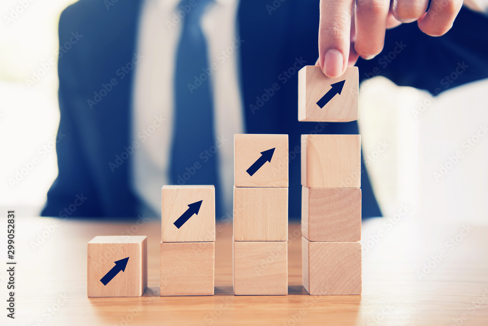 Fototapeta Business concept growth success process, Close up Businessman hand arranging wood cube with arrow stacking as step stair.