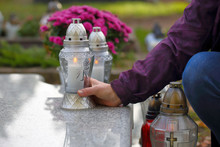 Women At The Cemetery Puts A Candle On The Grave