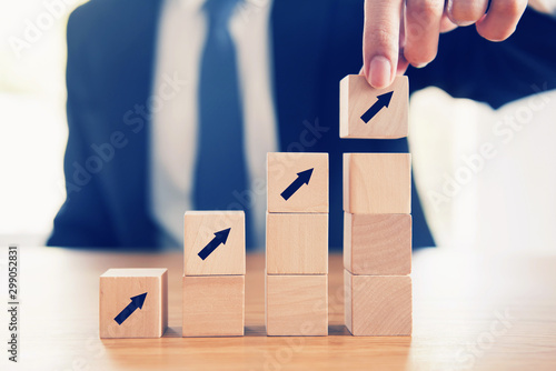 Cuadros en Lienzo Business concept growth success process, Close up Businessman hand arranging wood cube with arrow stacking as step stair