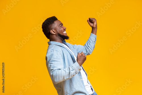 Leinwand Poster Portrait of excited african guy celebrating success with clenched fists