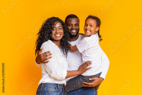 Fotografie, Tablou Young black parents with cute little daughter over yellow background