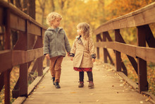 Boy And Girl Holding Hands Walking On Wooden Bridge In The Autumn Park