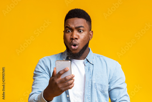 Astonished black guy looking at smartphone screen in shock Slika na platnu