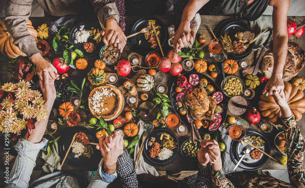 Fototapeta Family praying holding hands at Thanksgiving table. Flat-lay of feasting peoples hands over Friendsgiving table with Autumn food, candles, roasted turkey and pumpkin pie over wooden table, top view