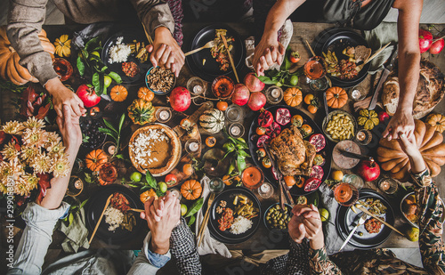 Family praying holding hands at Thanksgiving table. Flat-lay of feasting peoples hands over Friendsgiving table with Autumn food, candles, roasted turkey and pumpkin pie over wooden table, top view - 299058891