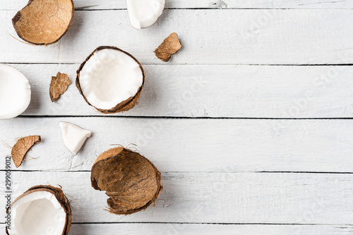 Overhead shot of coconut pieces on white wooden background with copyspace. Flat lay - 299059012