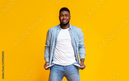 Fotografía Desperate african american guy showing empty pockets over yellow background
