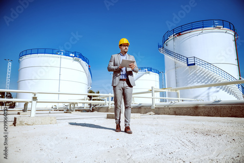 Fototapeta Full length of handsome caucasian businessman in suit standing outdoors and holding tablet. In background are oil storage tanks. obraz