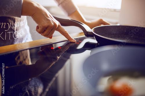 Cadres-photo bureau Macarons Close up of caucasian woman in apron adjusting temperature on stove. Breakfast preparation concept.
