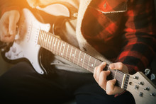 Stylish Young Musician In A Beautiful Plaid Jacket Plays Powerful Rock Music On A Black And White Electric Guitar, Illuminated By Bright Light.