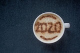 Mug of cappuccino with cinnamon under a cyanide color on a dark background.Cinnamon powder was sprinkled with 2020 figures on coffee foam.Symbol of New year in a cup on coffee foam on woolen fabric.