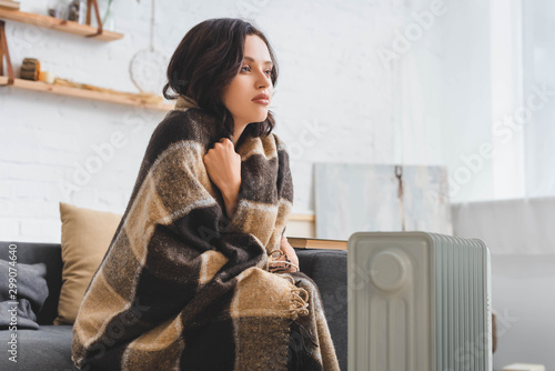 attractive girl warming up with blanket and heater in cold room