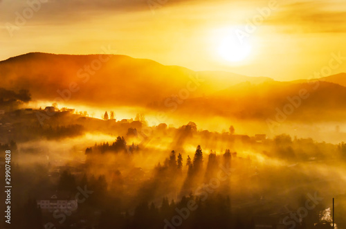 Fototapeta Bright misty sunrise in a mountain village obraz