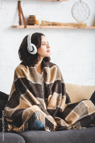 Obraz beautiful girl thinking and listening music with headphones while sitting in blanket - fototapety do salonu