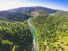 Beautiful Scenery Of A Narrow River Between The Mountains With A Lot Of Green Trees Under Clear Sky