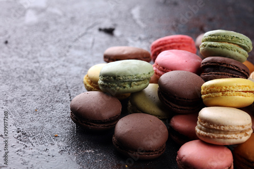 Sweet and colourful french macaroons or macaron on dark black background, Dessert.