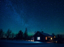 Cottage Against The Night Sky With The Milky Way And The Arctic Northern Lights Aurora Borealis In Snow Winter Finland