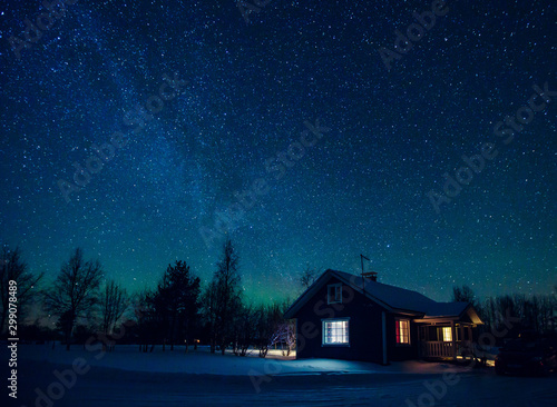 Papiers peints Route dans la forêt Cottage against the night sky with the Milky Way and the arctic Northern lights Aurora Borealis in snow winter Finland