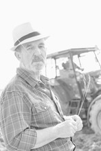 Black And White Photo Of Senior Farmer Standing Against Tractor In Field