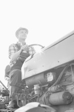 Black And White Photo Of Mature Farmer Driving Tractor In Field
