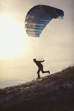 Silhouette Of An Athlete Running Down The Hillside Under The Filled With A Canopy Of Parachute Before The Flight. Speed Flying.