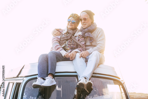 Fototapety, obrazy: Alternative travel lifestyle people with old senior retired couple sitting on the roof top of a vintage beautiful van enjoying the sunset - vacation holiday with camper vehicle and aged mature