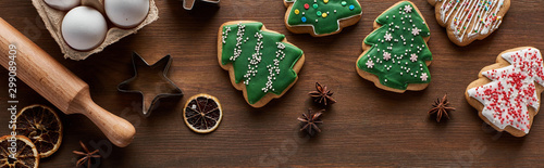 Fotomural  top view of Christmas tree cookies, dough molds, eggs and rolling pin on wooden
