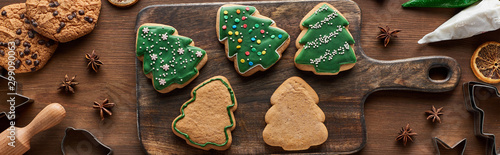 Door stickers Bread top view of glazed Christmas cookies with pastry bag on wooden cutting board, panoramic shot