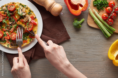 cropped view of woman eating on omelet from plate on table with fresh ingredients