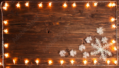 Fototapeta Christmas warm gold garland lights with snowflakes on wooden rustic background. Christmas or New Year concept obraz