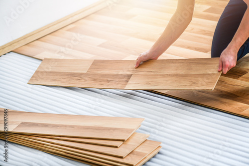 Obraz Worker hands installing timber laminate floor. Wooden floors house renovation with measure items. - fototapety do salonu