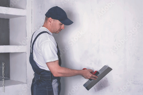 Fotomural Worker in overalls and cap plastering a wall with finishing putty using a putty knife