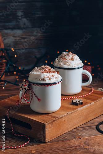 Printed kitchen splashbacks Chocolate Cozy Christmas composition.Two mug with hot drinks, chocolate with whipped cream and cinnamon stick on a dark wooden background. Sweet treats for cold winter days.