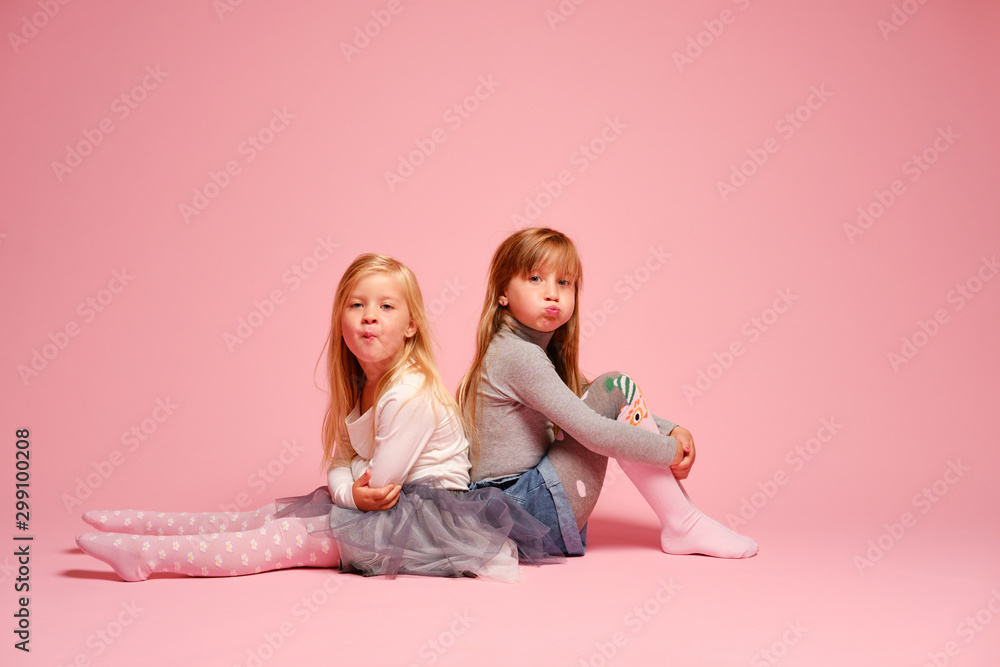 Fototapety, obrazy: Two little girls sit together on a pink background