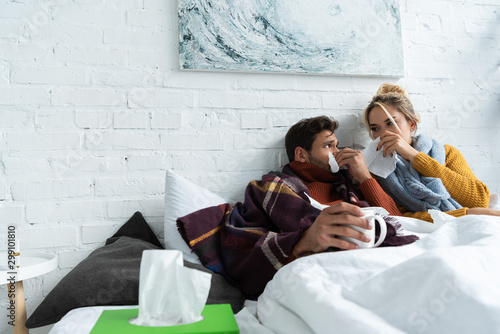 Valokuva  ill couple with runny noses lying in bed with napkins