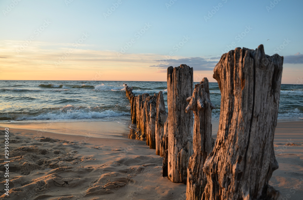 Fototapeta Wooden breakwater during sunset over the Baltic Sea, Uniescie, Poland.