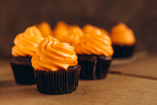 Stylish Festive Cupcake And Pumpkin On A Dark Background. Sweets For The Celebration Of Halloween