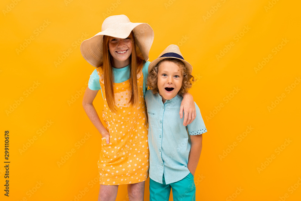 Fototapety, obrazy: funny brother with sister on orange wall background