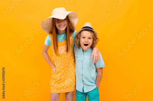 Fotografie, Tablou funny brother with sister on orange wall background