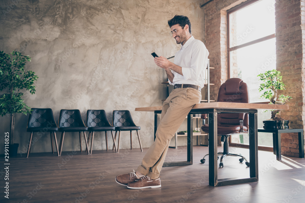 Fototapeta Full body profile side photo of confident smart middle eastern joyful businessman using smartphone send message to work colleagues partners feel content wear style pants trousers in loft office