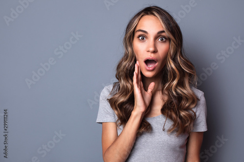Photo Closeup portrait of a beautiful surprised woman with hairstyle on gray background