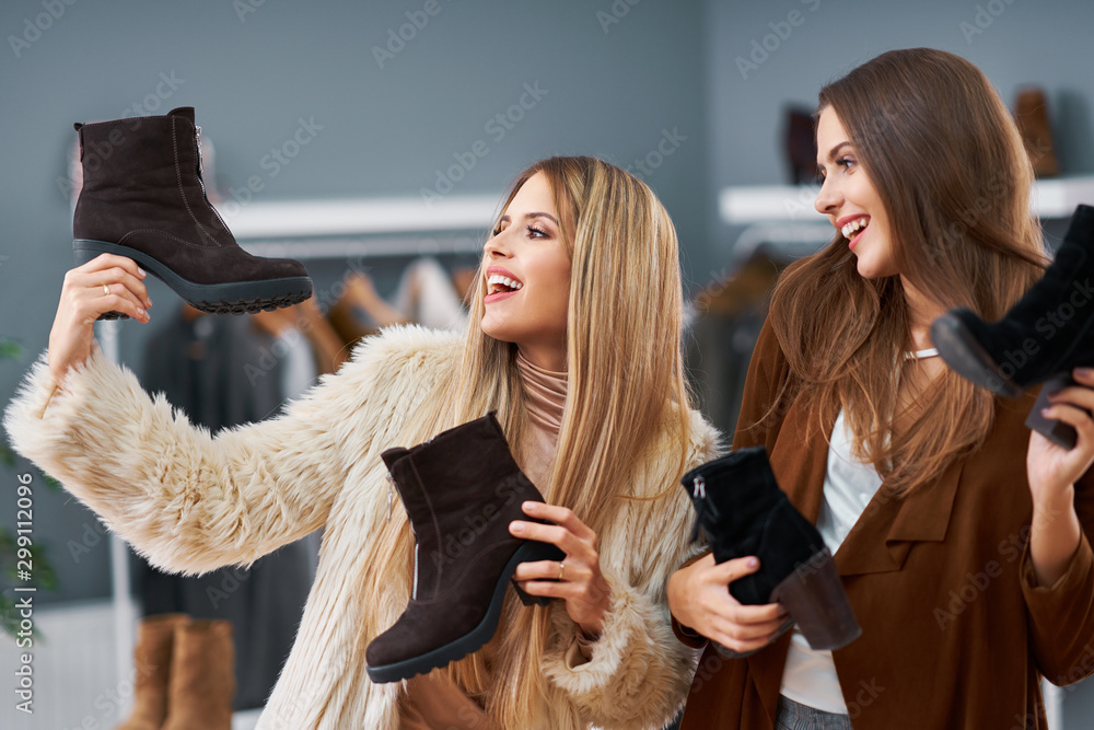 Fototapeta Adult women shopping for shoes in boutique in autumn