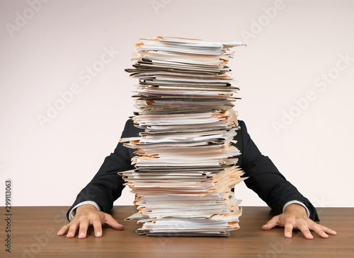 Fototapeta Young businessman hid behind with stack of papers on wooden table in room obraz