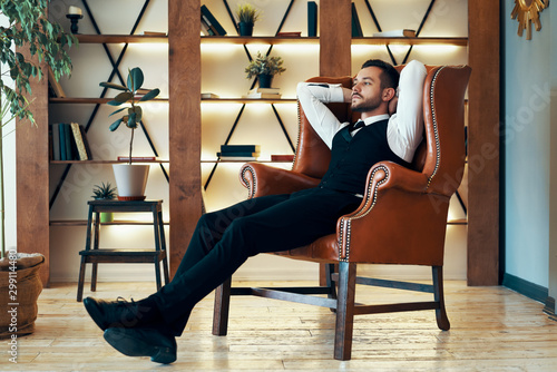 Pinturas sobre lienzo  Confident young man relax in armchair in luxury interior