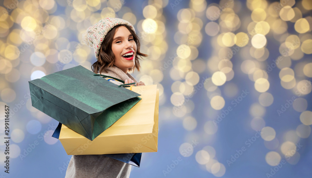 Fototapeta christmas, seasonal sale and consumerism concept - happy smiling young woman in knitted winter hat and sweater with shopping bags over festive lights on blue background