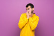 canvas print picture - Handsome man with yellow sweatshirt nervous and scared putting hands to mouth
