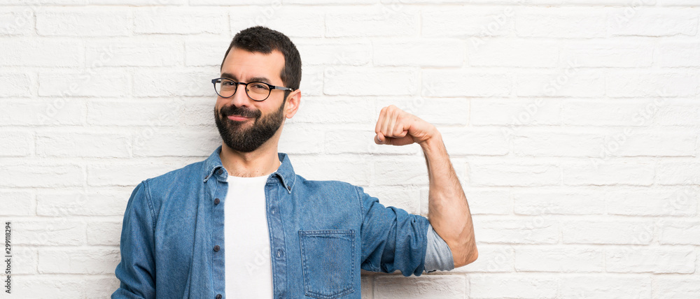 Fototapeta Handsome man with beard over white brick wall doing strong gesture