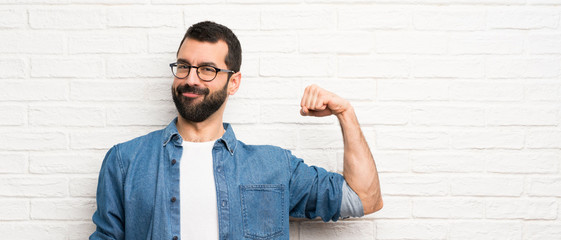 Handsome man with beard over white brick wall doing strong gesture