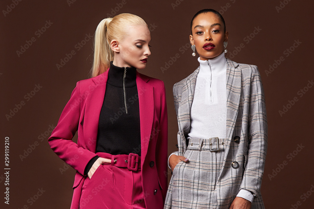 Fototapeta Two sexy beautiful woman fashion glamour model brunette blond hair makeup wear suit trousers jacket clothes every day casual office dress code party style accessory date walk skinny body shape studio.