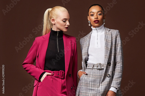 Obraz Two sexy beautiful woman fashion glamour model brunette blond hair makeup wear suit trousers jacket clothes every day casual office dress code party style accessory date walk skinny body shape studio. - fototapety do salonu